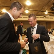 Lukas Rosol (L) and Lleyton Hewitt exchange gifts at the official team dinner for the Davis Cup World Group tie between Australia and Czech Republic; Pavel Lebeda