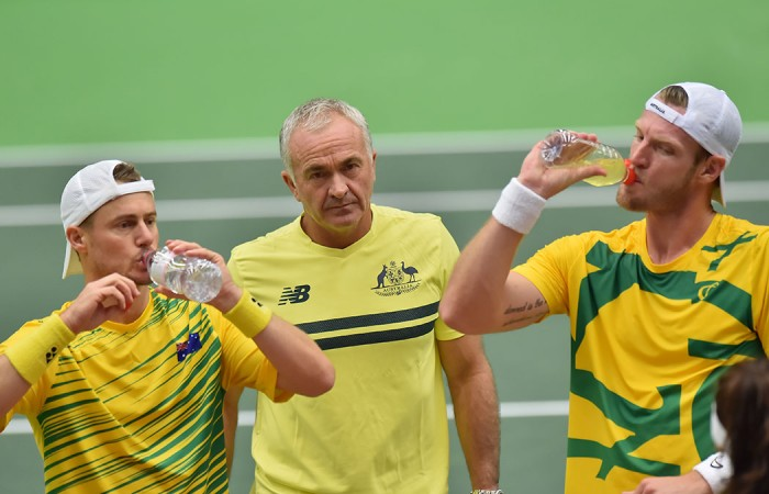 Lleyton Hewitt and Sam Groth take a break watched by Davis Cup captain Wally Masur.