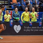 Casey Dellacqua (L) is cheered on by teammates during the second singles rubber of the Netherlands v Australia Fed Cup World Group Play-off tie in 's-Hertogenbosch; Henk Koster