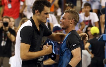 Bernard Tomic (L) shakes hands with Lleyton Hewitt after winning their second-round US Open match in five sets on Grandstand; Getty Images