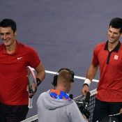 Bernard Tomic (L) and Novak Djokovic share a nice moment at net after Djokovic won their Shanghai Masters quarterfinal; Getty Images