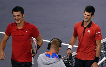 Bernard Tomic (L) and Novak Djokovic share a nice moment at net after Djokovic won their Shanghai Masters quarterfinal; Getty Images