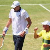 John Isner (L) walks past Australian captain Lleyton Hewitt during the reverse singles rubber of the Australia v United States Davis Cup World Group tie at Kooyong; Getty Images