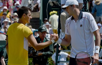 John Isner (R) shakes hands with Bernard Tomic after winning the reverse singles rubber of the Australia v United States Davis Cup World Group tie at Kooyong; Getty Images