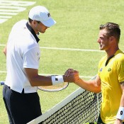 John Isner (L) shakes hands with Sam Groth after winning the opening singles rubber of the Australia v United States Davis Cup tie at Kooyong Lawn Tennis Club; Getty Images
