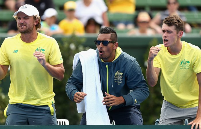 (L-R) Matt Reid, Nick Kyrgios and Alex De Minaur cheer from the sidelines during Australia's Davis Cup World Group first-round win over the Czech Republic at Kooyong; Getty Images