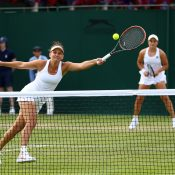 Casey Dellacqua plays a volley as Ash Barty watches on during their first-round win at Wimbledon; Getty Images