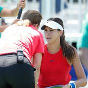 Ajla Tomljanovic consults with the trainer before retiring from her first-round match in Stanford; Getty Images