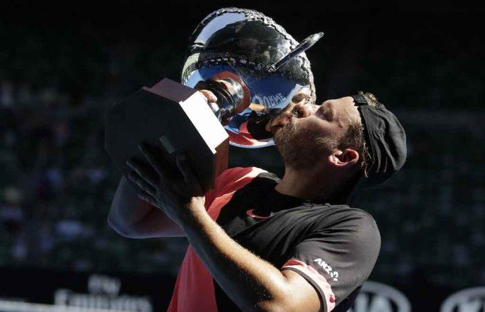 Dylan Alcott kisses the trophy having defended his Australian Open title.