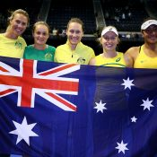 The Australian Fed Cup team pose with the Aussie flag after winning their World Group Play-Off tie against the Netherlands in Wollongong; Getty Images