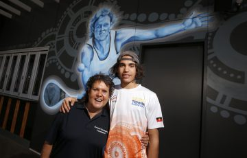 DARWIN, AUSTRALIA - AUGUST 29: Evonne Goolagong Cawley and Zachary Scott stand in front of a mural of Evonne painted by a group of local artists, including David Collins and Indigenous artists Shaun Lee 'Hafleg' and Jesse Bell to celebrate and recognise her incredible achievements during the National Indigenous Tennis Carnival at the Darwin International Tennis Centre on August 29, 2019 in Darwin, Australia. (Photo by Darrian Traynor/Getty Images)