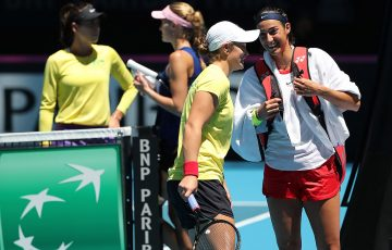 The Australian and French Fed Cup teams chat as they cross over between practice sessions at RAC Arena in Perth. (Getty Images)