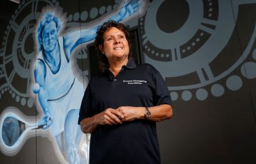 Evonne Goolagong Cawley stands in front of a mural of her painted by a group of local artists, including David Collins and Indigenous artists Shaun Lee 'Hafleg' and Jesse Bell to celebrate and recognise her incredible achievements during the National Indigenous Tennis Carnival at the Darwin International Tennis Centre.