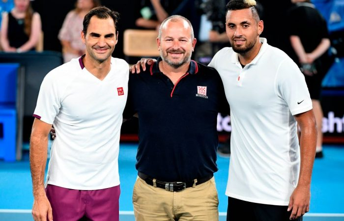 SHOWING SUPPORT: Roger Federer and Nick Kyrgios with a volunteer firefighter during the AO Rally for Relief event at Rod Laver Arena in January. Picture: Getty Images