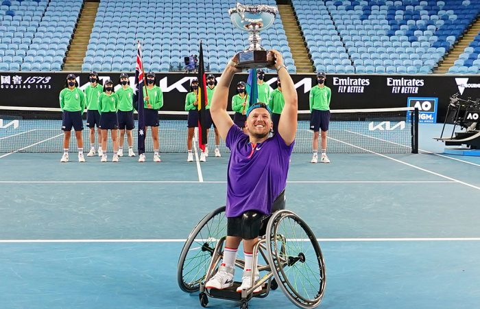 Dylan Alcott lifts an Australian Open quad wheelchair singles trophy for the seventh time.